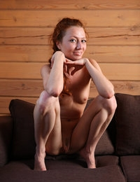 Petite Kesy in the brown sofa giving a clear view of her nude body and twat
