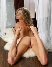 Elegant blonde seductress Ginny raises her leg to reveal her twat